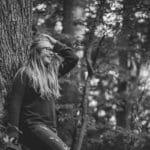 Teen girl leaning against tree.