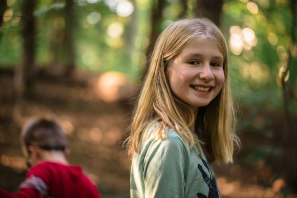Girl smiling at camera in the forest.