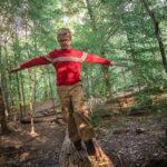 Boy walking on log in the woods.