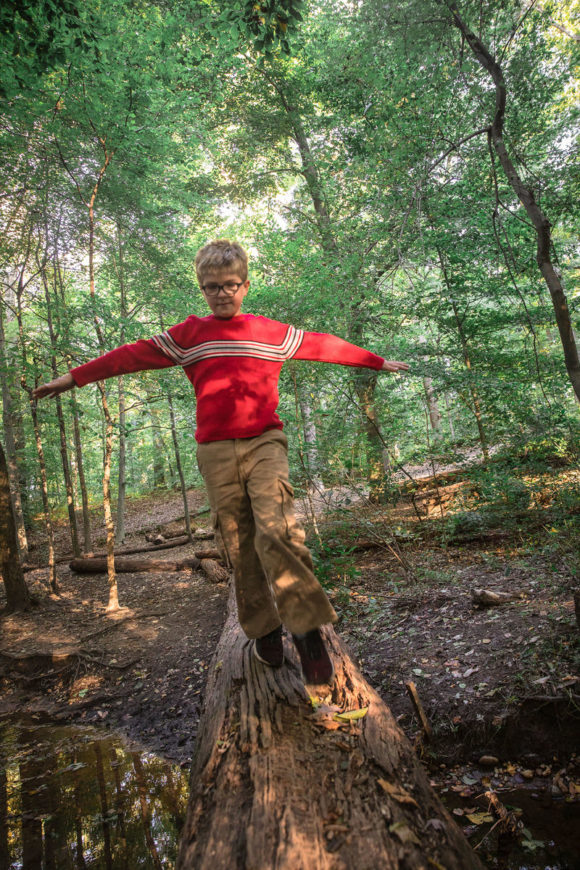 Boy walking on log in the woods.