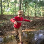Boy crosses creek on stepping stones.