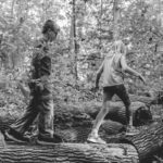Boy and girl walking in woods.
