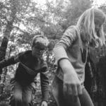 Close up of boy and girl walking in woods.