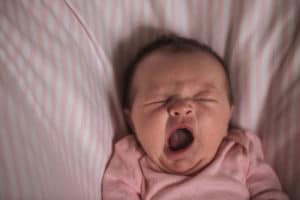 Newborn baby yawns.