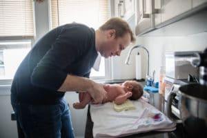 Father washing newborn baby in kitchen.