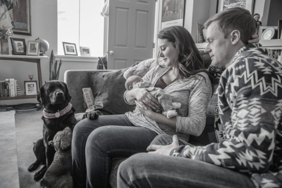 Mother and father hold baby on couch.