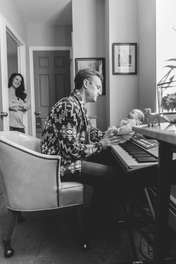 Father and newborn at piano.