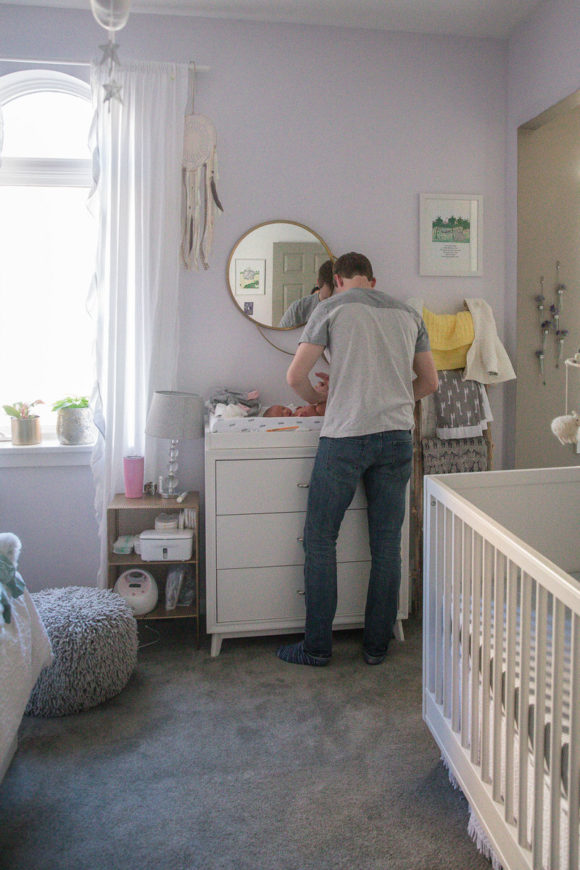 Father and baby at changing table in nursery.