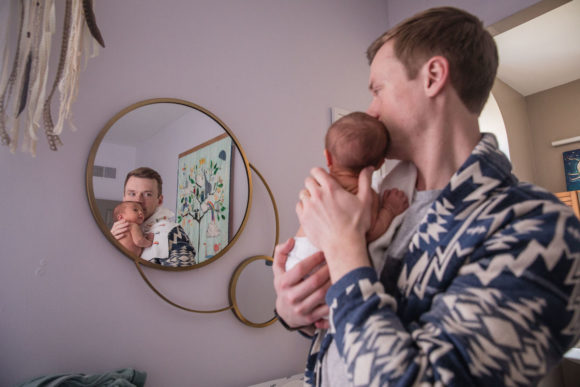 Father and baby look in nursery mirror.